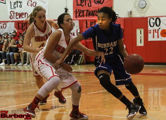 Yazzy Sa'dullah of Burbank managed to score 22 points despite a superb defensive effort by Burroughs' Delaney Nicol (Photo by Ross A. Benson)