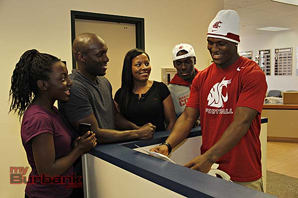 With his parents, brother and sister by his side, James prepares to FAX over his LOI to Wazzou (Photo By Edward Tovmassian)