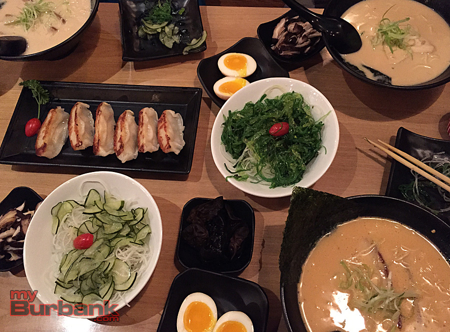 Bowls of ramen surround seafood gyoza, cucumber salad and seaweed salad. Soup additions of soft-boiled eggs and mushrooms dot the table. (Photo By Lisa Paredes)