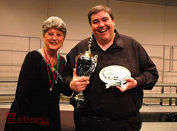 A Cappella Scholarship Festival Chair Pat Kahmann, left, presents trophy to Brendan Jennings, director of John Burroughs Powerhouse choir, which took home $7,500 on Saturday. (Photos by Joyce Rudolph)