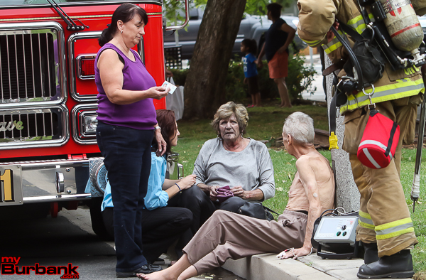 Smoke inhalation victims await Fire Dept treatment after they were pulled from a house fire at 1307 Chandler Street Monday afternoon. (Photo by © Ross A. Benson)