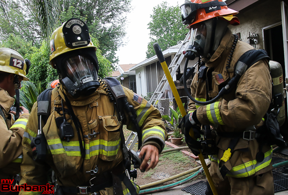 Burbank Firefighters work at the scene of a house fire Monday afternoon. Photo by © Ross A. Benson)
