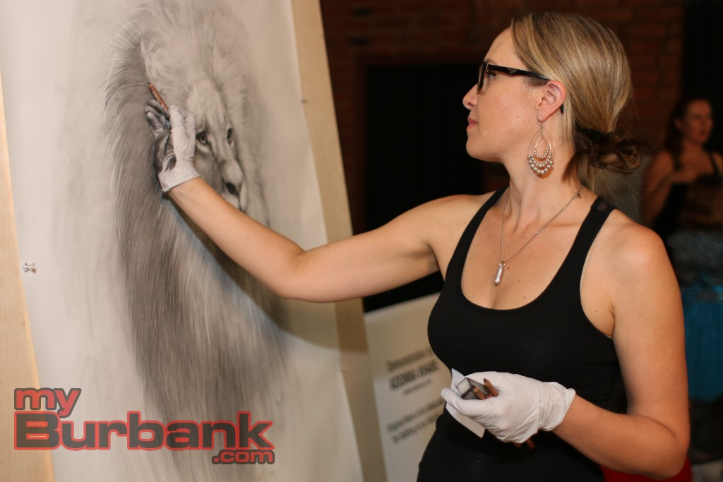 Adonna Khare puts on a demonstration at the Secret Art Show on Saturday as she works on an enormous drawing of a lion. Photo by: Edward Tovmassian