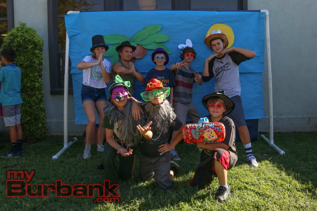 Luther students enjoy the wacky props offered to them at the photo booth as the pose for a photo at Luther Burbank Middle School on Friday during the Luther Beach Party. Photo By: Edward Tovmassian