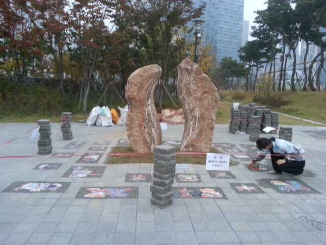 """A worker installs tiles and pavers around the """"Dancing Stones"""" sculpture in Incheon, South Korea. (Photo courtesy City of Burbank)"""