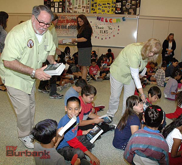 Burbank Elks members and husband and wife, Greg and Charlene Peale, distribute dictionaries to third-graders at Providencia Elementary School.