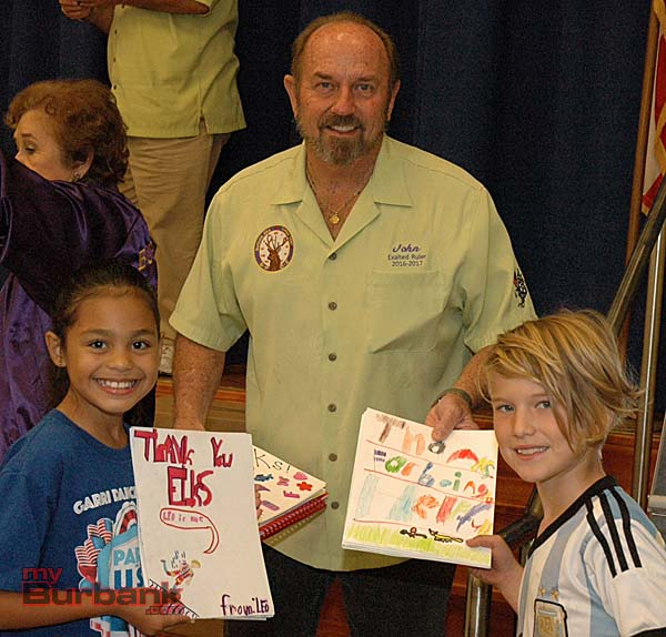 Burbank Elks Lodge Exalted Ruler John Coyle receives thank-you notes from Noel Mason, left, and Leo Gersh, both students in Kelly Ohrt's third-grade class.