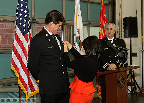 Chief Tom Lenahan gets pinned with his new badge by his wife Irene, as Assistant Chief Kenet Robertson looks on. (Photo by Ross A. Benson)