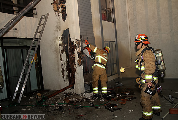 Burbank Fire Fighters cut into the walls to extinguish a stubborn wall fire. (Photo by Ross A. Benson)