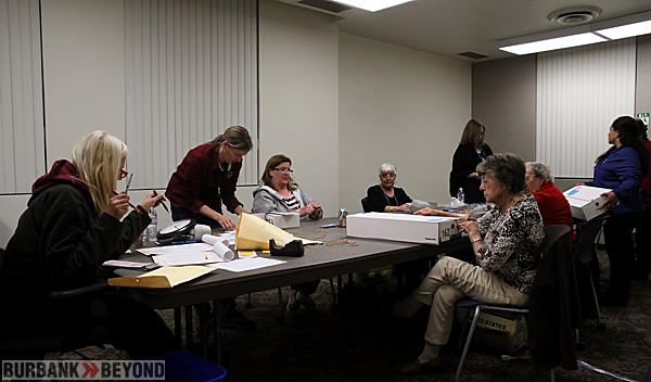 In an office in the City Clerks office, several people gather ballots and time stamp them, and prepare them for counting. (Photo by Ross A. Benson)