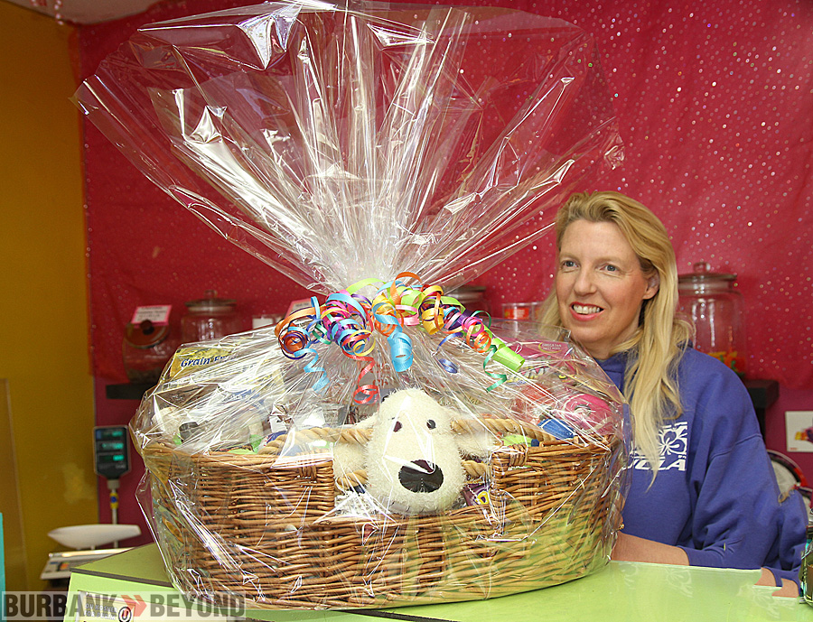 Peggy Woods Pet Emporium Manager Jenny Dehl displays the gift basket that will be raffled off. (Photo by Ross A. Benson)