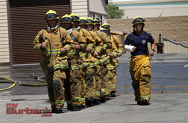 """Chanting their class motto: """"Together in Stride, Centennial Pride"""" Burbank's newest fire fighters jog into place during graduation exercises Friday. (Photo by Ross A. Benson)"""