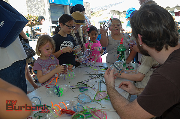Brandon Carlson woks with some of the younger attendees as they take used water bottles and make different types of bugs (Photo By Craig Sherwood)