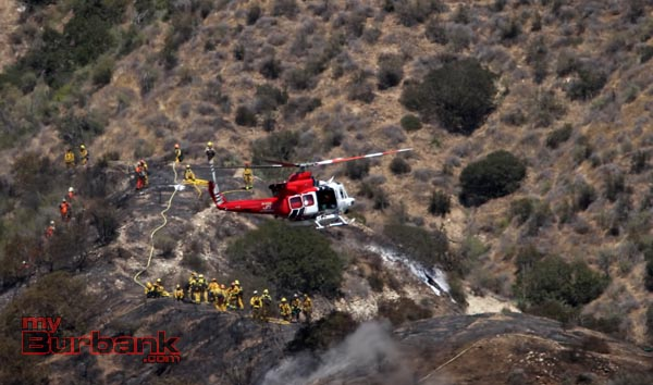 LA City Fire Helicopter brings hose and refreshments to fire crews high on a hill above DeBell Golf Course. (Photo by Ross A. Benson)