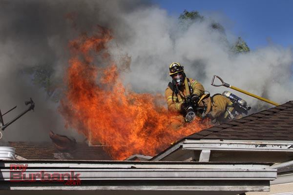Burbank Firefighters work at ventilating this attic fire and putting water on the flames at a residence in the 700 Blk of Kenwood Street Thursday afternoon. (Photo by Ross A. Benson)