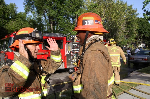 Burbank Fire Captain Mark Hatch talks with Captain Tray White at the scene of house fire Thursday afternoon. (Photo by Ross A. Benson)