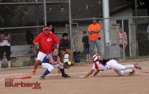 A Burroughs runner is thrown out at third base in the Bulldogs win (Photo by Ross A. Benson)