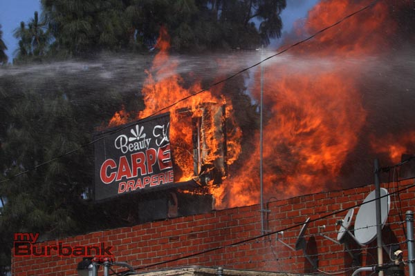 Flames consume the overhead sign in front of Beauty Kiss Carpets & Draperies. (Photo by Ross A. Benson)