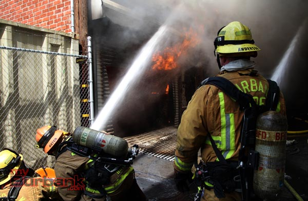 Firefighters aim water at flames to the rear of Beauty Kiss Carpets. (Photo by Ross A. Benson)