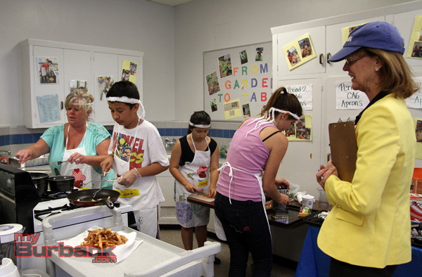 Burbank's new Mayor Emily Gabal-Luddy a judge watch one of the team prepare their meal. (Photo by Ross A. Benson)