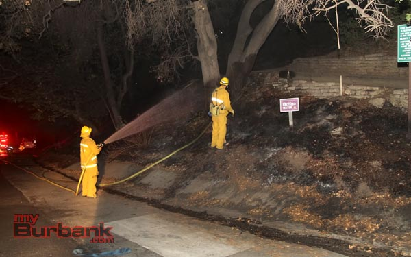 Burbank Firefighter wet down the area where a small brush fire occurred near Wildwood Cyn. (Photo by Ross A. Benson)