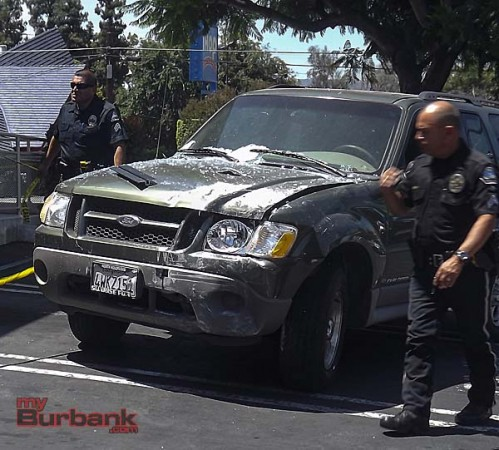 Burbank Police look over damage to the car that hit the building  (Photo By Nick Colbert)