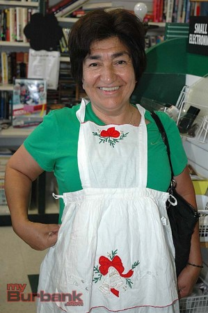 Regular customer Josefina Castellon models a holiday apron while shopping during the Christmas in July Sale at La Providencia Guild Children's Hospital Thrift Shop  (Photo By Joyce Rudolph)