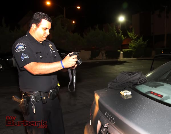 Burbank Police Sergent Claudio Losacco takes a picture for evidence of a wad of $100 bills that was recovered from the suspects car. (Photo by Ross A. Benson)
