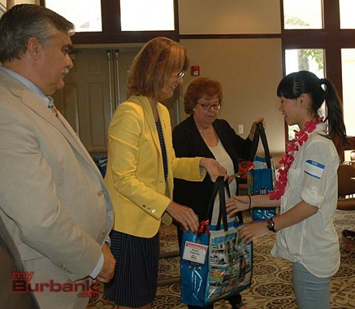 Councilman Jess Talamantes, left, watches as Mayor Emily Gabel-Luddy presents a city of Burbank Centennial tote bag to Ota student Yuka Saito while Library Services Director Sharon Cohen readies another souvenir bag   (Photo By Joyce Rudolph)