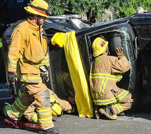 Firefighters remove the windshield so a woman could get out of the vehicle  (Photo By Craig Sherwood)