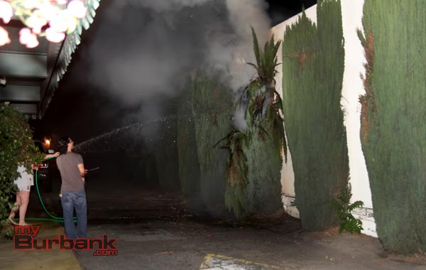 Civilians grabbed a garden hose prior to the Fire Departments arrival and knocked down a good part of the fire next to Samuel's Florist. (Photo by Ross A. Benson)