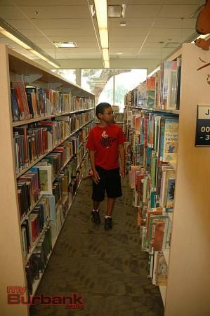 Jaden Stewart, 9, strolls through the children's section of Northwest Library on Saturday     (Photo By Joyce Rudolph)