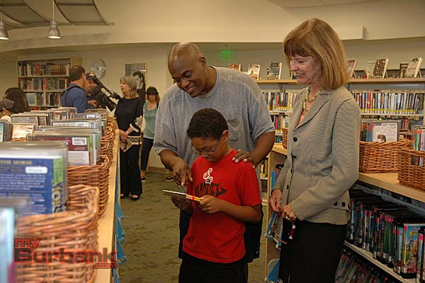 John Stewart and his son, Jaden, check out a DVD while talking to Mayor Emily Gabel-Luddy about the renovation of Northwest Library     (Photo By Joyce Rudolph)