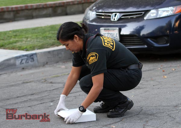 Forensic Specialist Nancy Robles collects evidence of a gun that was tossed from a suspect on Elmwood. (Photo by Ross A. Benson)