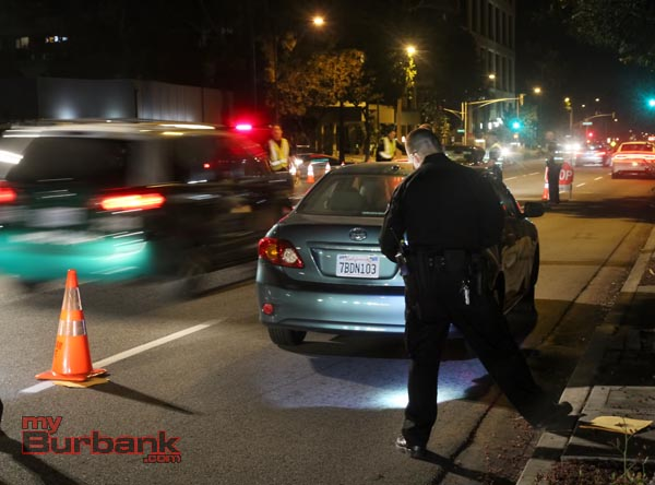 Burbank Police Traffic Officer Todd Fatta cites a driver for being unlicensed, before allowing his passenger to drive away from DUI checkpoint. (Photo by Ross A. Benson)