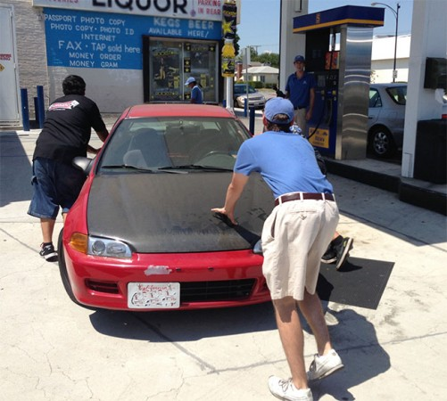 Robbie and Ron Perez get a little help from the Helpful Honda Guy pushing their 1994 Civic to the gas pump. (Photo by Stan Lynch)