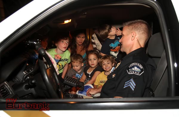 Burbank Police Sgt. John Pfrommer gives a group of kids a full tour of his office, or police cruiser at one of the block parties during National Night Out.(Photo by Ross A. Benson)
