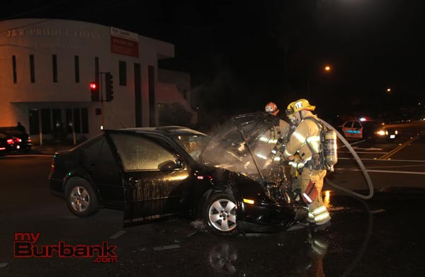 Burbank Firefighters wet down the engine of this auto following it catching fire after it was involved in a non-injury accident at Hollywood Wy & Alameda St. (Photo by Ross A. Benson)