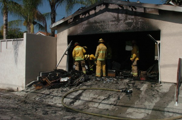 Firefighters work on clearing a garage after a fire early Friday morning (Photo By Nick Colbert)