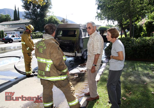 Ed Ricksecker and his wife talk to Capt. Mark Hatch after his beloved 77 VW Van caught fire Sunday afternoon.(Photo by Ross A. Benson)
