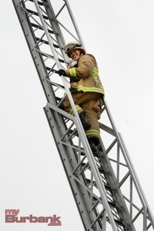 Firefighter Donan pauses mid-climb for some encouragement from the children below. (Photo By Ross A. Benson)