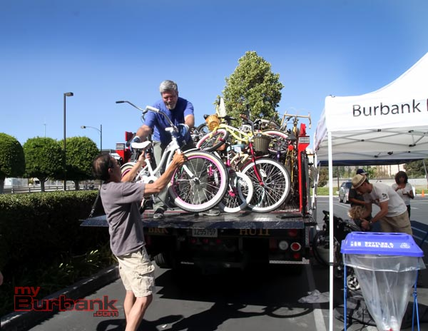 Bike Angel Jorge Martinez hands up a donated bike to the truck full. (Photo by Ross A. Benson