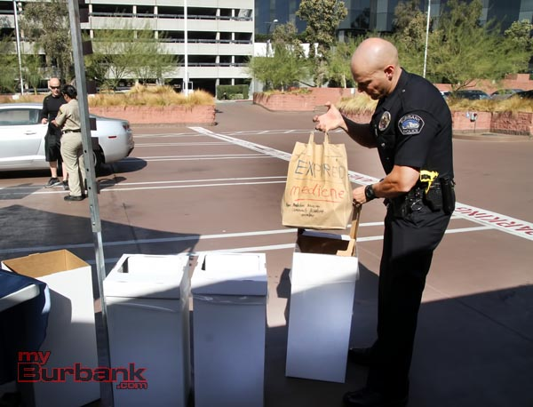 Burbank Police Officer Joshua Kendrick of the COPS Bureau takes a bag of expired medicines during Saturdays Drug Take Back Program. (Photo by Ross A. Benson)