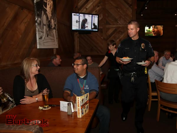 "Burbank Police Sgt. John Pfrommer serves dinner during 'Tip A Cop"" event at Black Angus. (Photo by Ross A. Benson)"