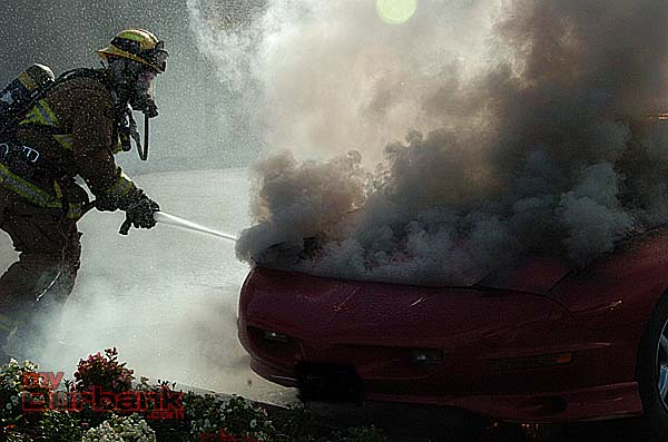 A firefighter applies water to a Camaro which caught on fire (Photo By Nick Colbert)