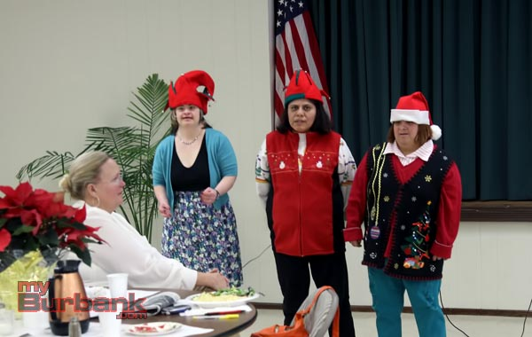 In keeping with the theme of the Holiday Basket Program at the Coordinating Council's meeting this week, three students from BCR a place to grow, sang Christmas carols.  Pictured from L-R are singers Chrissy, Karen, and Sandy.  Seating in the foreground is BCR Executive Director Julie Larsen. (Photo By Ross A. Benson)