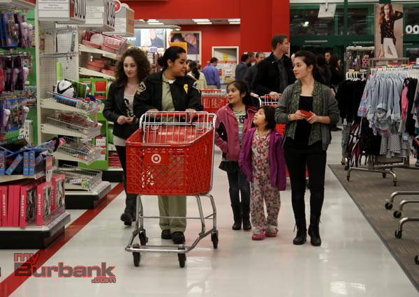 "Burbank Police Officers, Explorers, Cadets and Volunteers teamed up with Burbank Noon Rotary members at Target at the Empire Center Thursday evening and held this years""Heroes and Helpers"". The kids were given gift cards and went through the store picking gifts for family members.Pictured is Police Cadat Magdalena Bautista with a group heading for the toy isles. (Photo by Ross A. Benson)"