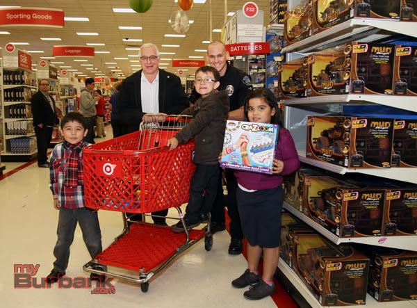 "Burbank Police Officers, Explorers, Cadets and Volunteers teamed up with Burbank Noon Rotary members at Target at the Empire Center Thursday evening and held this years""Heroes and Helpers"". The kids were given gift cards and went through the store picking gifts for family members.Pictured are Burbank Noon Rotary Member Barry Gusow along with BPD Motor Officer Ryan Murphy with a couple of kids looking for the good deals.(Photo by Ross A. Benson)"
