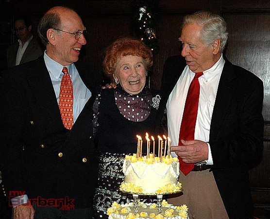 Grace Mylroie Patz, celebrating her 100th birthday, prepares to blow out the candles on her cake with help from her sons Gerry Mylroie, left, and Jim Mylroie on Sunday at Lakeside Golf Club. (Photo by Joyce Rudolph)