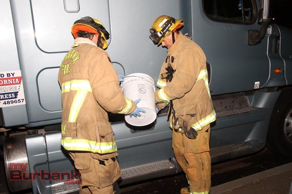Fire Fighters saved several gallons and returned the fuel to another truck. ( Photo by Ross A. Benson)